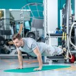 Last pushups. Young and handsome athlete doing pushups in the gy — Stock Photo