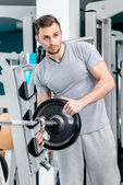 Man with  loads post dumbbells — Stock Photo