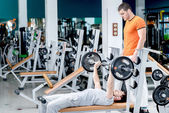 Bench press. Two athletes engaged in the simulator room. One you — Stock Photo