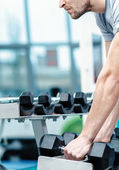 Load on the biceps. Successful athlete working out with dumbbell — Stock Photo