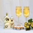 Christmas composition with two wine glasses, a small house-holder and candles. — Stock Photo #35503307