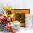 Christmas composition with clock, glasses and a thick silver candle.Theme song for the clock. — Stock Photo