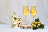 Christmas composition with two wine glasses, a small house-holder and candles. — Stock Photo
