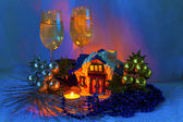 Christmas composition - ceramic house,two of groceries with champagne, beads and candles. Silver and gold. — Stock Photo