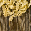 Raw pasta on wood background — Stock Photo