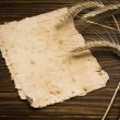 Wheat on the old wooden table and old paper — Stock Photo
