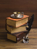Old books and pen on a wooden table — Stock Photo