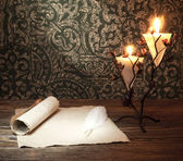 Old paper with a candle and a quill pen — Stock Photo