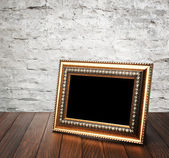 Old photo frame on the wooden table — Stock Photo