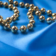 Christmas necklace against blue silk — Stock Photo