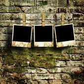 Bilder auf einem seil mit wäscheklammer mit beschneidungspfad für bilder, vor einer mauer — Stockfoto