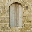 Boarded up window of antique building — Stock Photo