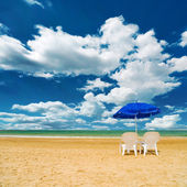 Pair of sun loungers and a beach umbrella on a deserted beach — Stock Photo