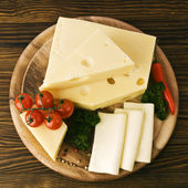 Arrangement with appetizing cheese on the kitchen cutting board. — Stock Photo