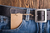 Vintage paper tag on blue denim — Stock Photo