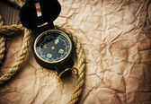 Old compass and rope on grunge background — Stock Photo