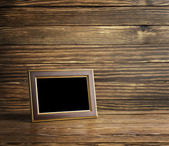 Photo frame on old wooden table — Stock Photo