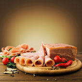 Fresh ham slices with lattuce and cherry tomato on the wooden board — Stock Photo