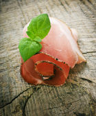 Cured ham on wooden ground — Stock Photo