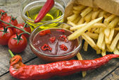 French fries with ketchup oil, tomatoes and chili peppers — Stock Photo