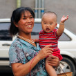 BEIJING, CHINA - JULY 4: Happy chinese woman with a baby in her arms, Beijing, China — Stock Photo #38648673