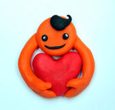 Plasticine smiling man with a big heart — Stock Photo