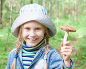 Cute little girl picking mushrooms in the forest — Stock Photo
