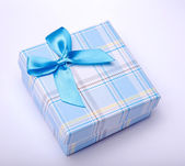 Blue gift box with ribbon - on isolated white — Stock fotografie