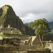 Ruins inside Machu Picchu, Peru with cloudy sky and sun peeking through and Wayna Picchu in the background — Stock Photo