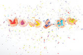 Red, blue, yellow and green pencil shaving on white background — Stock Photo