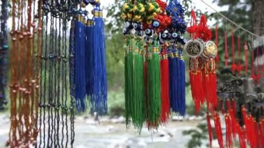 Color Mongolian amulets to protect the premises from evil spirits sway in the wind before the fast mountain river — Stock Video
