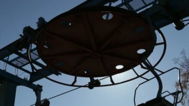 HD. Large horizontal wheel with holes bearing rope chair lift turns to a dark blue sky and sun — Stock Video