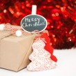 Wrapped Christmass gift box on red sparkling background — Stock Photo