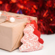Wrapped gift box on red sparkling background — Stock Photo
