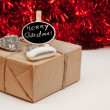 Wrapped Christmass gift box with sign on red sparkling backgrou — Stock Photo