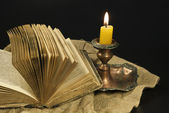 Old open book and burning candle on linen cloth — Stock Photo