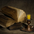 Old books with yellow candle on canvas background — Stock Photo