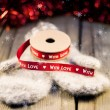 Knitted mittens with ribbon decoration With love on wooden backg — Stock Photo #35794909