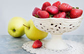 Apples and strawberries in a vase on the marble background. — Stock Photo