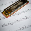 Note sheet and harmonica — Stock Photo