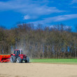 Red tractor on an acre in spring — Stock Photo