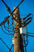 Confuse cables on a wooden pole — Stock Photo