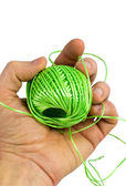 Hand and ball of green fiber — Stock Photo