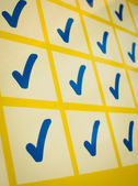 Blue checkmarks in yellow grid — Stock Photo