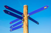 Wooden pole with numerous direction arrows — Foto Stock