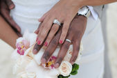 Wedding couple hands with rings on flowers — Stock Photo
