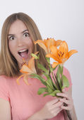 Surprised girl with flowers — Stock Photo