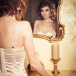 Brunette woman with curly hairstyle standing near luxury mirror — Stock Photo #49963881