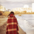 Brunette woman outdoors in check pattern plaid standing near the lake with her back on us. Copy space — Stock Photo #49964435