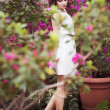 Portrait of a beautiful brunette woman in pink dress and colorful make up outdoors in azalea garden — Stock Photo #49966111